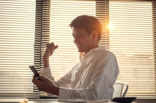 Empresário feliz após receber boas notícias para conseguir um novo emprego no smartphone