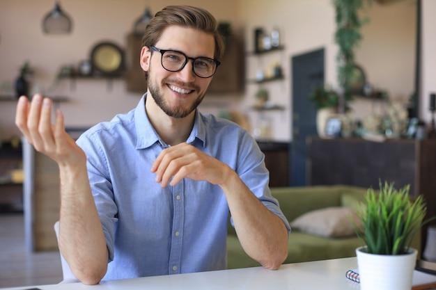 Empresário feliz confiante em óculos, sentado no local de trabalho em casa e olhando para a câmera.