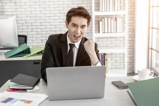 Empresário feliz e bem-sucedido trabalhando em um laptop