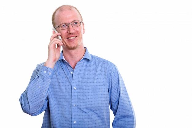Empresário feliz e pensativo sorrindo enquanto fala no celular