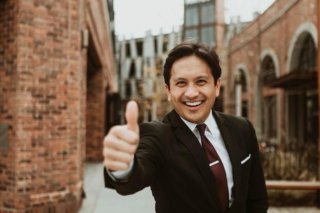 Empresário feliz fazendo sinal de positivo na cidade