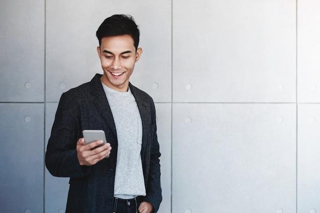 Empresário feliz usando o smartphone. lendo mensagem via celular