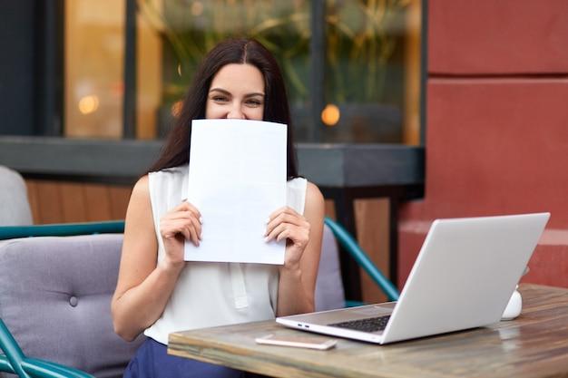 Empresário feminino morena atraente detém papel perto do rosto, sorri positivamente, usa computador portátil para fazer relatório de negócios