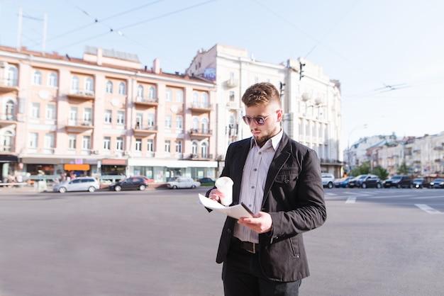 Empresário fica com uma xícara de café e documentos na mão sobre a rua da cidade