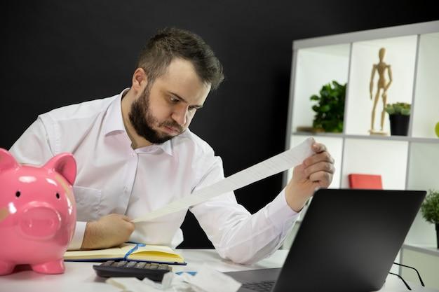 Empresário frustrado, olhando para as contas longas nas mãos, piggybank quebrado