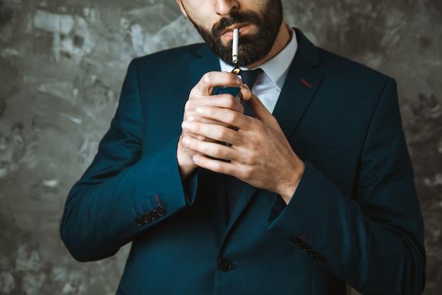 Empresário fumando um cigarro em fundo escuro