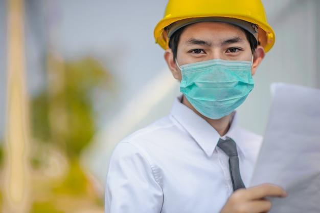 Empresário gerente usar máscara facial capacete amarelo segurando blueprint trabalho construção civil