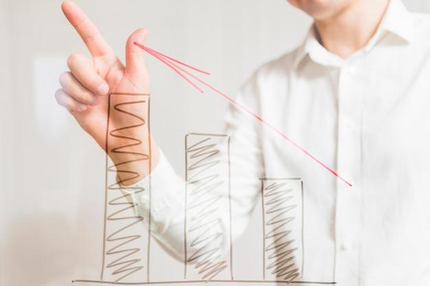 Empresário gesticulando atrás de gráficos crescentes com a seta vermelha na placa de vidro
