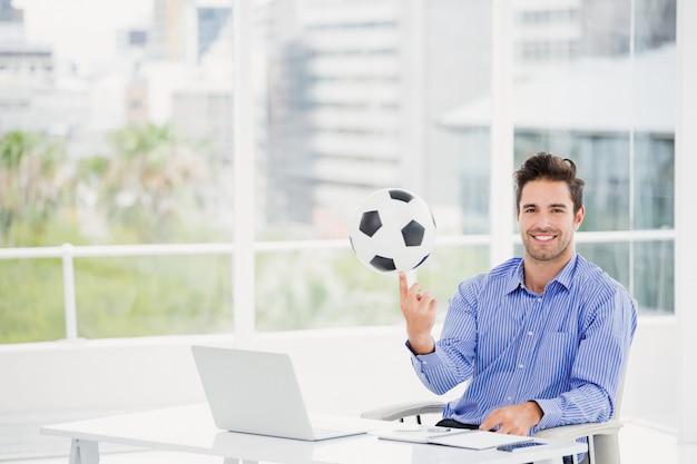 Empresário girando uma bola de futebol no dedo