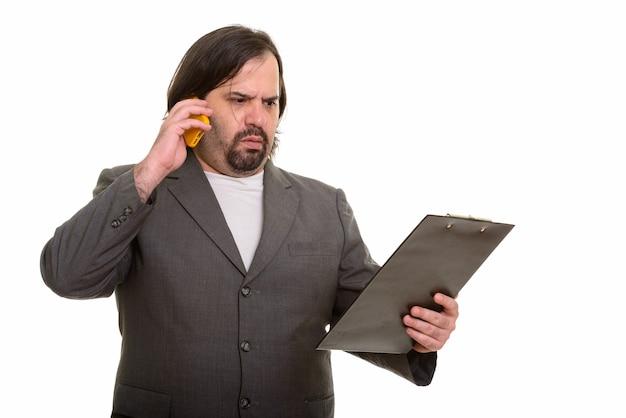 Empresário gordo e caucasiano parecendo confuso enquanto fala ao telefone e lê na prancheta