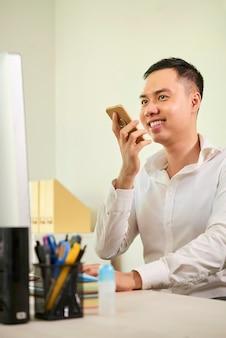 Empresário, gravando uma mensagem de áudio no telefone