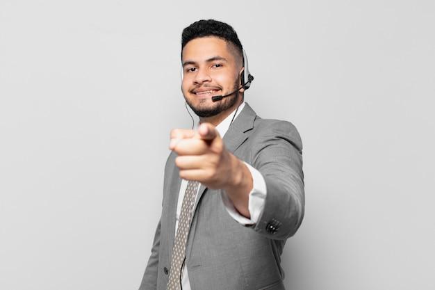 Empresário hispânico apontando ou mostrando o conceito de operador de telemarketing