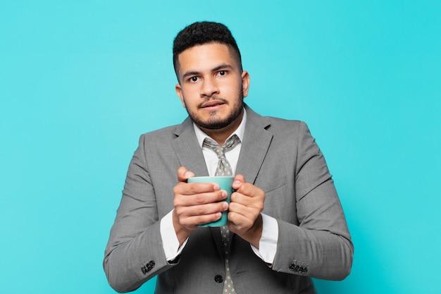 Empresário hispânico com expressão assustada e segurando uma caneca de café