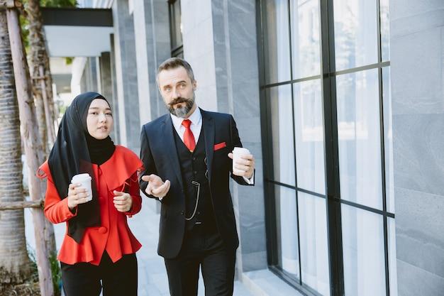 Empresário hispânico com mulheres de negócios muçulmanos árabes asiáticos conversando durante a pausa para o café em um prédio de escritórios moderno.