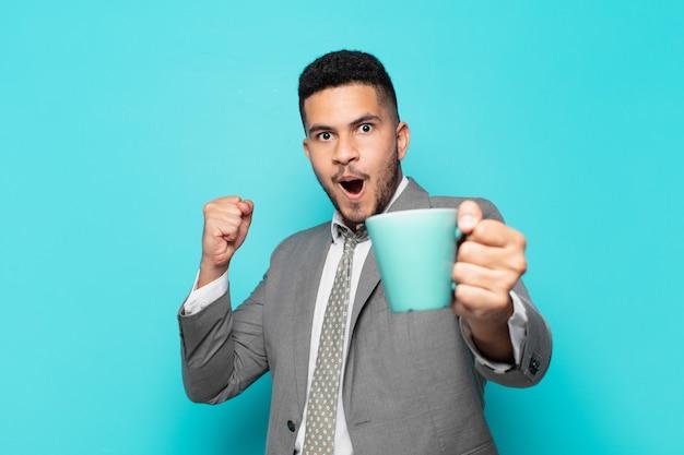 Empresário hispânico comemorando vitória de sucesso e segurando uma caneca de café