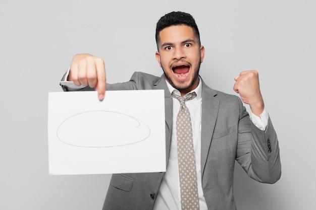 Empresário hispânico comemorando vitória de sucesso e segurando uma folha de papel