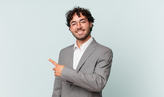 Empresário hispânico parecendo animado e surpreso, apontando para o lado e para cima para copiar o espaço