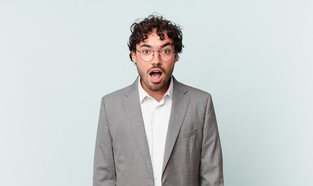 Empresário hispânico parecendo muito chocado ou surpreso, olhando com a boca aberta dizendo uau