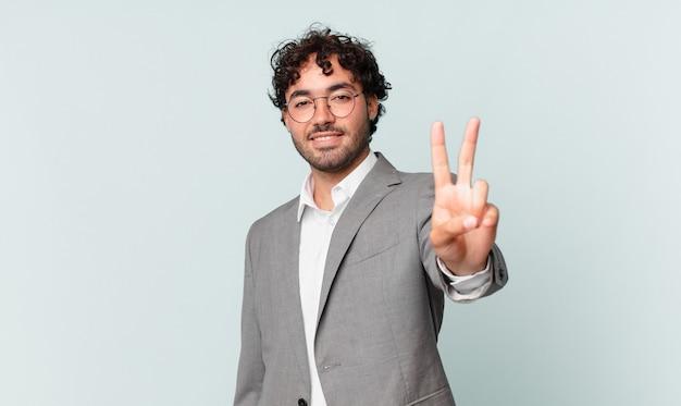 Empresário hispânico sorrindo e parecendo feliz, despreocupado e positivo, gesticulando vitória ou paz com uma mão