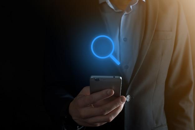 Empresário, homem segura na mão ícone de lupa. conceito de negócio, tecnologia e internet