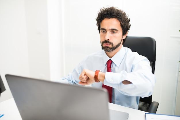 Empresário impaciente cheirando enquanto assistia seu relógio de pulso