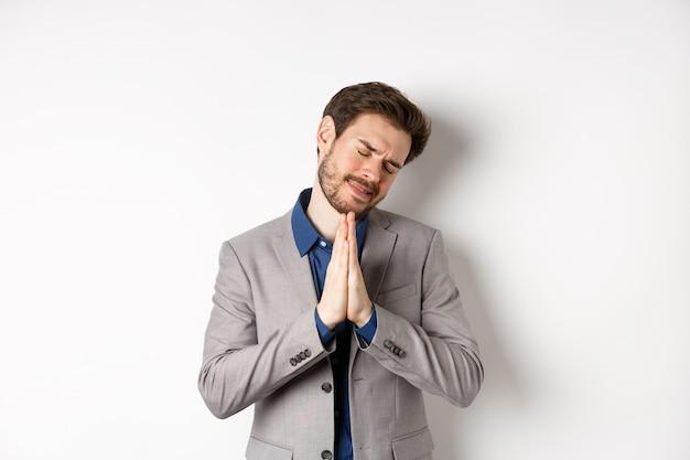 Empresário implorando implorando por ajuda, de mãos dadas em oração e pedindo favor