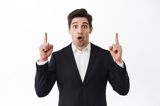 Empresário impressionado, empresário de terno preto ofegante, diga uau e aponte para copyspace, mostrando o anúncio superior, parede branca