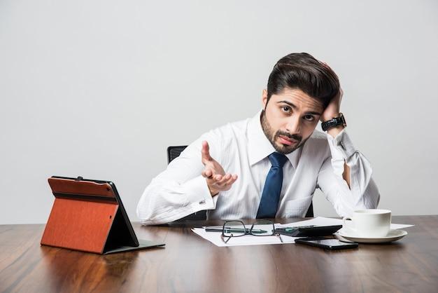 Empresário indiano barbudo, contando enquanto está sentado à mesa da escrivaninha no escritório