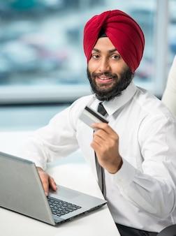 Empresário indiano com laptop e cartão de crédito.