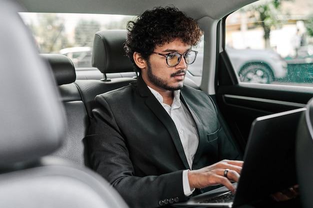 Empresário indiano no banco de trás trabalhando.