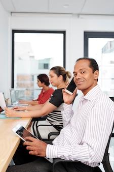 Empresário indiano sorridente à mesa no espaço de coworking, ele verifica e-mails no tablet e atende ligações