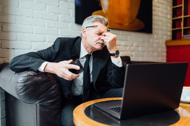 Empresário infeliz de meia-idade em restaurante moderno usando laptop e telefone.