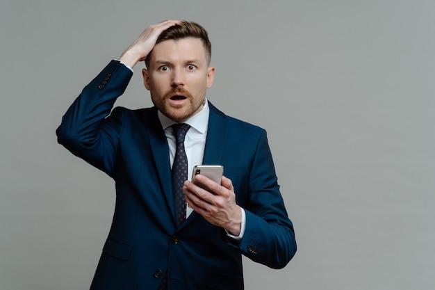 Empresário infeliz de terno segurando o celular e recebendo más notícias desagradáveis, olhando para a câmera com a boca aberta e expressão de rosto chocado em pé contra um fundo cinza. conceito de falha