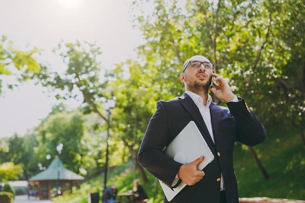 Empresário inteligente bem sucedido na camisa branca, terno clássico, óculos. homem ficar com o computador laptop pc, falar no celular no parque da cidade ao ar livre no fundo da natureza. escritório móvel, conceito de negócio.