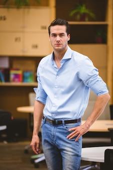 Empresário inteligente com mão no quadril em pé na sala de reuniões
