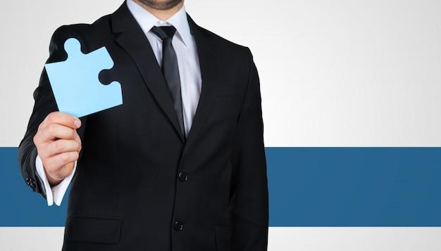 Empresário irreconhecível, segurando a peça do quebra-cabeça. conceito de negócios
