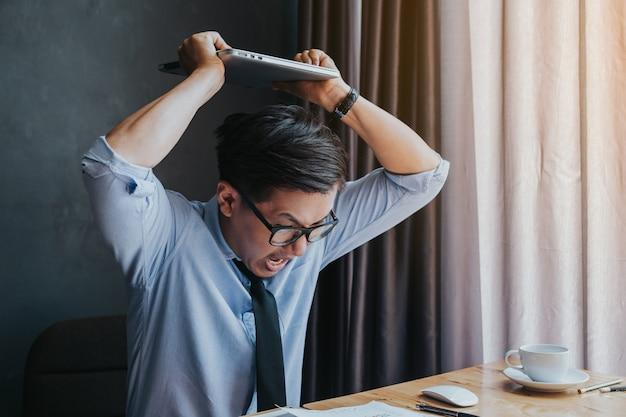 Empresário irritado, esmagando seu laptop porque o negócio não é como o esperado.