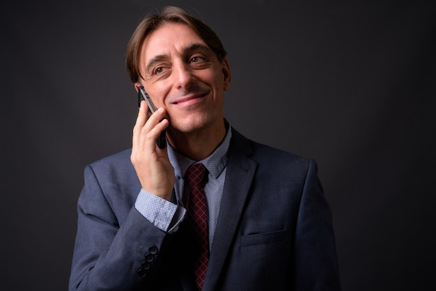 Empresário italiano bonito maduro contra parede cinza