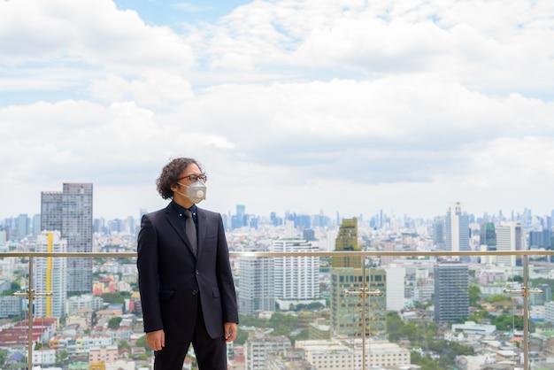 Empresário japonês com cabelo encaracolado em terno e máscara para proteção contra surto de coronavírus contra vista da cidade