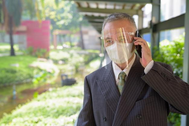 Empresário japonês maduro com máscara e escudo facial, falando ao telefone no parque