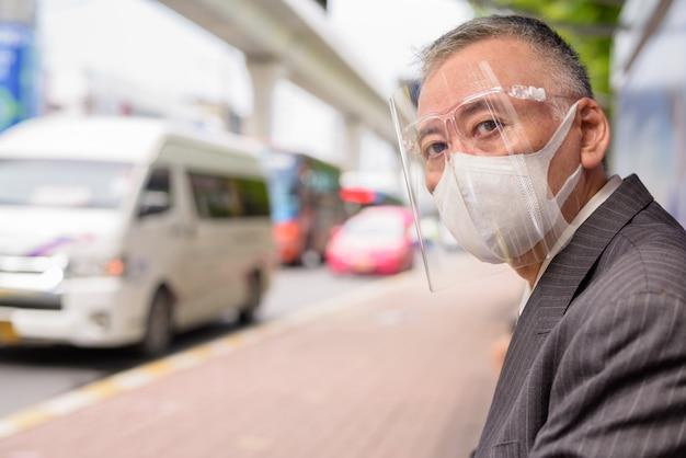 Empresário japonês maduro com máscara e escudo facial, sentado no ponto de ônibus