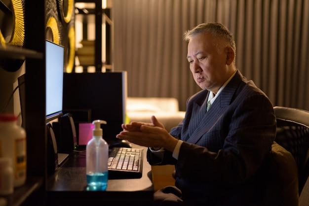 Empresário japonês maduro, usando desinfetante para as mãos enquanto trabalhava horas extras em casa tarde da noite