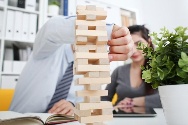 Empresário joga em uma estratégia de mão jenga