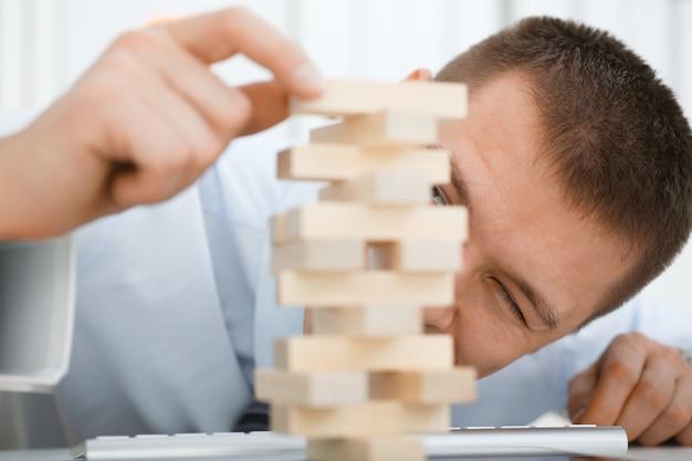 Empresário joga na mão de estratégia, reorganizando os blocos de madeira envolvidos durante a pausa no trabalho no escritório sentado mesa jogos pilha diversão conceito de passatempo de alegria