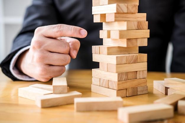 Empresário jogando o jogo de madeira, mãos do executivo colocando o bloco