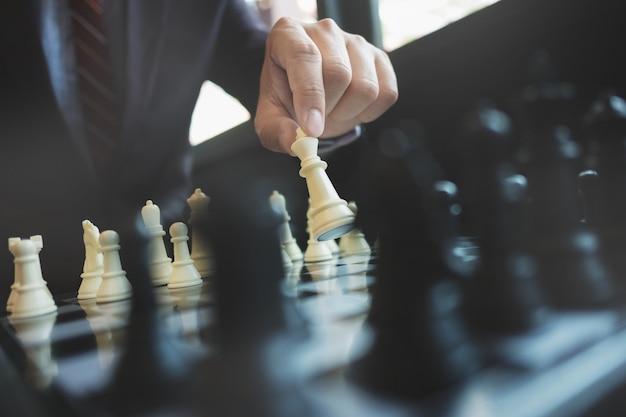 Empresário jogando xadrez a bordo no escritório, estratégia e conceito de competição