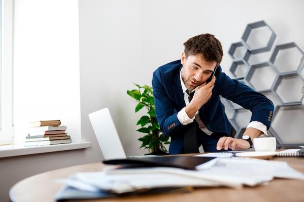 Empresário jovem distraído, falando no telefone, plano de fundo do escritório.