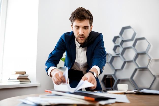 Empresário jovem distraído remexendo nos papéis, fundo do escritório.
