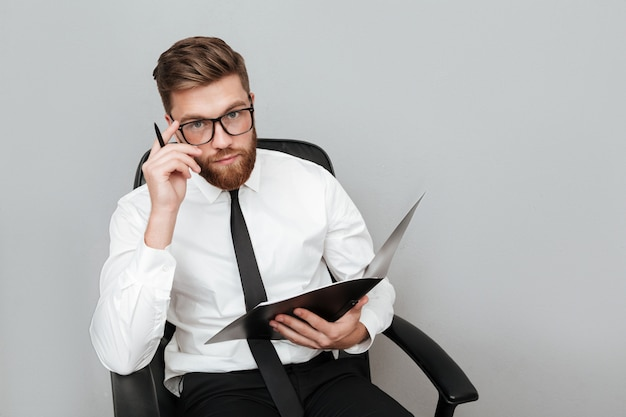 Empresário jovem pensativo em óculos, segurando uma pasta