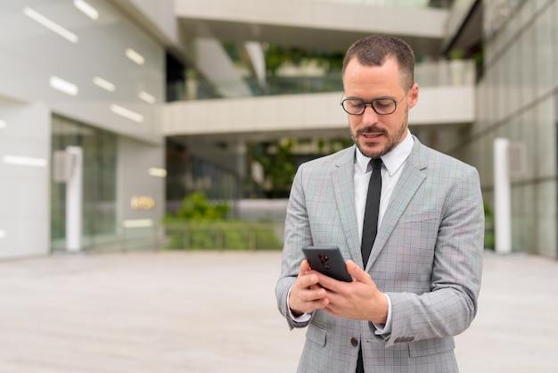 Empresário latino-americano de barba careca usando telefone com óculos na cidade ao ar livre